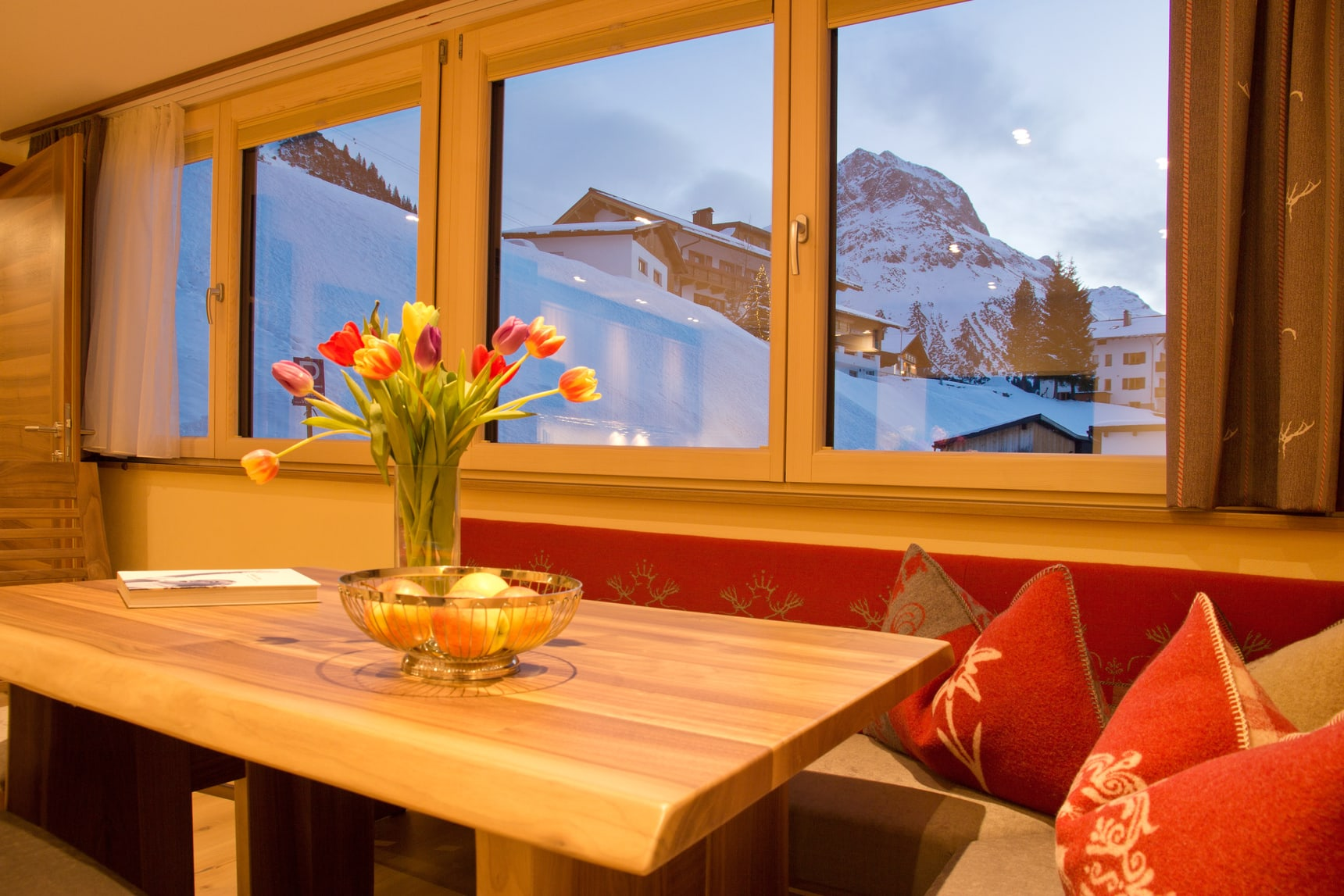Flowers sit on a wooden table next to a window view of beautiful snow covered Lech.