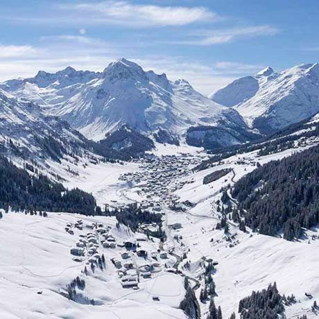Snow covered mountain, trees and houses view in sunny Lech am Arlberg